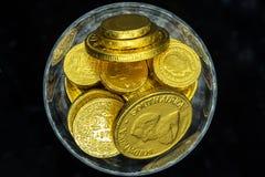 Ett exponeringsglas av guld- mynt Royaltyfria Bilder
