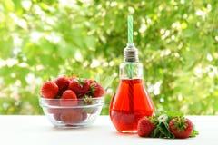 Ett exponeringsglas av jordgubbefruktsaft En bunke med jordgubbar Royaltyfria Foton
