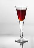Ett exponeringsglas av körsbärsröd likör Royaltyfri Bild
