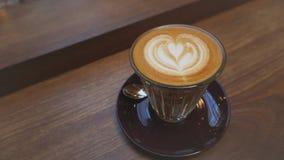 Ett exponeringsglas av kaffe med bruna tefat arkivbilder