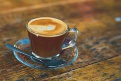Ett exponeringsglas av kaffe på en trätabell arkivfoton