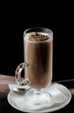 Ett exponeringsglas av kakao på en mörk bakgrund Arkivfoton