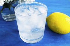 Ett exponeringsglas av kallt vatten med is och citronen p? en bl? bakgrund royaltyfri fotografi