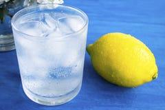 Ett exponeringsglas av kallt vatten med is och citronen p? en bl? bakgrund arkivbild