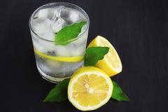 Ett exponeringsglas av kallt vatten med omkring is, citronen och mintkaramellen p? en bl? bakgrund arkivbilder