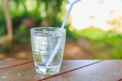 Ett exponeringsglas av kallt vatten på en trätabell arkivfoton