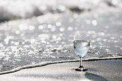 Ett exponeringsglas av kolsyrat vatten på en sandig strand på en ljus dag Stilsepiasignal royaltyfria foton