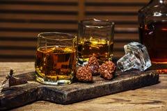 Ett exponeringsglas av konjak eller whisky på en lantlig tabell med choklad royaltyfri foto