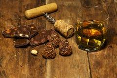 Ett exponeringsglas av konjak eller whisky på en lantlig tabell med choklad royaltyfri fotografi