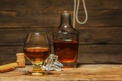 Ett exponeringsglas av konjak eller whisky på en lantlig tabell med choklad arkivfoton