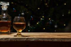 Ett exponeringsglas av konjak eller whisky på en lantlig tabell med choklad arkivbilder