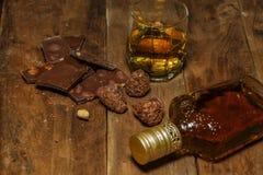 Ett exponeringsglas av konjak eller whisky på en lantlig tabell med choklad royaltyfria foton