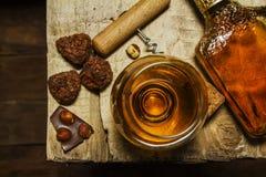 Ett exponeringsglas av konjak eller whisky på en lantlig tabell med choklad arkivfoto