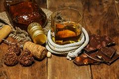 Ett exponeringsglas av konjak eller whisky på en lantlig tabell med choklad royaltyfri bild
