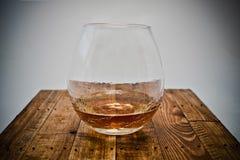 Ett exponeringsglas av konjak på träbakgrund Arkivbild