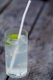 Ett exponeringsglas av lemonad och ett sugrör på en trätabell Alkoholcoctail med limefrukt och uppiggningsmedel på en grov träbak Royaltyfria Bilder