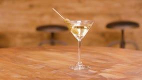Ett exponeringsglas av martini med oliv på en trätabell arkivfilmer