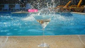 Ett exponeringsglas av martini nära pölen flickan dyker in i pölen lager videofilmer