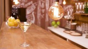 Ett exponeringsglas av martini på en stångräknare i en tom restauranginre stock video