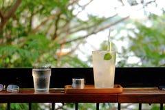 Ett exponeringsglas av med is citronläsk på träbänk med grön naturbakgrund royaltyfria foton