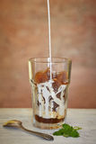 Ett exponeringsglas av med is kaffe och spill mjölkar arkivfoto