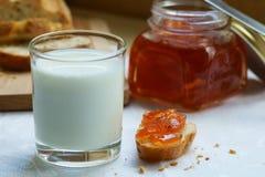 Ett exponeringsglas av mjölkar med ett stycke av bröd och driftstopp Fotografering för Bildbyråer