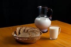 Ett exponeringsglas av mjölkar, mjölkar panerar en kanna av och Royaltyfri Bild
