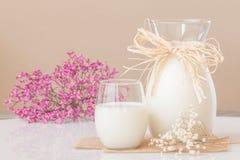 Ett exponeringsglas av mjölkar, och en kanna av mjölkar på marmortabellen Royaltyfria Bilder