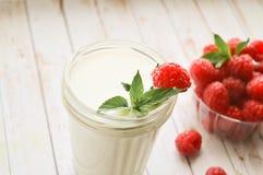 Ett exponeringsglas av mjölkar och nya hallon med mintkaramellen på en vit bakgrund, närbild Sund riktig näring banta frukter arkivfoto