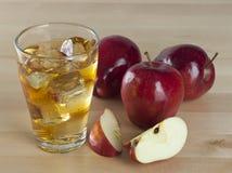 Ett exponeringsglas av ny kall äppelmust med is bredvid äpplen på A Wo Royaltyfria Bilder