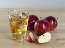 Ett exponeringsglas av ny kall äppelmust med is bredvid äpplen på A Wo Royaltyfri Bild