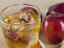 Ett exponeringsglas av ny kall äppelmust med is bredvid äpplen på A Wo Arkivfoto