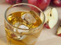 Ett exponeringsglas av ny kall äppelmust med is bredvid äpplen på A Wo Arkivbilder