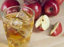 Ett exponeringsglas av ny kall äppelmust med is bredvid äpplen på A Wo Royaltyfria Foton