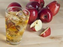 Ett exponeringsglas av ny kall äppelmust med is bredvid äpplen på A Wo Arkivbild