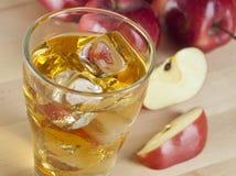 Ett exponeringsglas av ny kall äppelmust med is bredvid äpplen på A Wo Arkivfoton