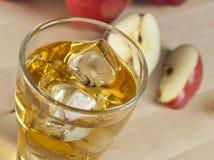 Ett exponeringsglas av ny kall äppelmust med is bredvid äpplen på A Wo Royaltyfri Foto