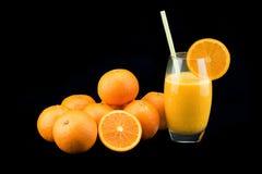 Ett exponeringsglas av ny orange fruktsaft med den mogna orange högen Arkivfoto