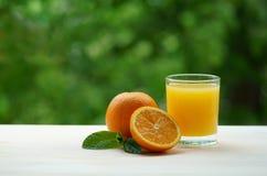 Ett exponeringsglas av ny orange fruktsaft med en skiva av apelsin- och mintkaramellsidor Royaltyfria Foton