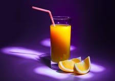 Ett exponeringsglas av ny orange fruktsaft med ett sugrör och skivor av apelsinen Violett bakgrund och göra mörkare runt om kante royaltyfri fotografi