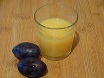 Ett exponeringsglas av ny orange fruktsaft och två plommoner arkivfoto