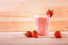 Ett exponeringsglas av nya och söta smoothies för smak, på ett ljus - brun trätabell Några jordgubbar är nära en krus av jordgubb Arkivfoton
