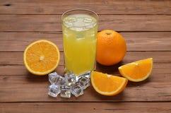 Ett exponeringsglas av nya orange fruktsaft och apelsiner på en gammal trätabell Royaltyfri Fotografi