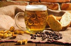Ett exponeringsglas av nytt kallt ljust öl med bröd på säckväv arkivfoto