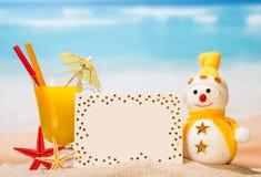 Ett exponeringsglas av orange fruktsaft med, det tomma kortet, snögubben och sjöstjärnan I Royaltyfri Fotografi