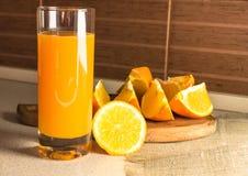 Ett exponeringsglas av orange fruktsaft och orange skivor på tabellen arkivfoton