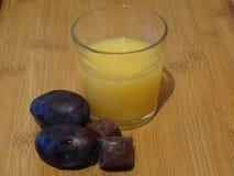 Ett exponeringsglas av orange fruktsaft, plommoner och choklad royaltyfri fotografi
