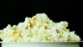 Ett exponeringsglas av popcorn på en svart bakgrund Roterar långsamt Royaltyfri Bild