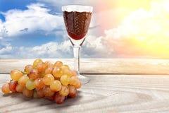 Ett exponeringsglas av rött vin med druvor på en trätabell mot en bakgrund av moln arkivbilder