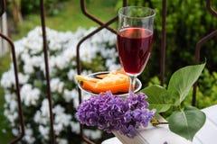 Ett exponeringsglas av rött vin med ost på balkongen av huset i f royaltyfri bild